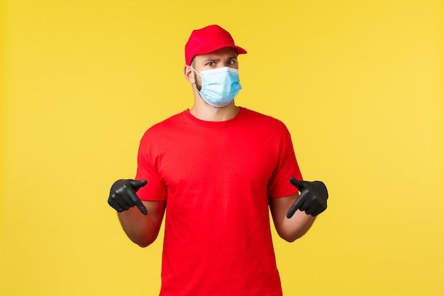 Ekspresowa dostawa podczas pandemii, covid-19, bezpieczna wysyłka, koncepcja zakupów online. zdezorientowany i niepewny kurier pytający o promo, zdziwiony i skierowany w dół, załóż maskę medyczną