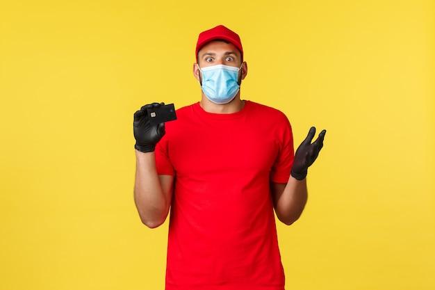 Ekspresowa dostawa podczas pandemii, covid-19, bezpieczna wysyłka, koncepcja zakupów online. zszokowany kurier nie może zrozumieć, co się stało, pokazując kartę kredytową, podnosząc rękę zaskoczony, nosząc maskę medyczną.
