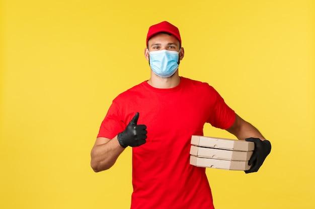 Ekspresowa dostawa podczas pandemii, covid-19, bezpieczna wysyłka, koncepcja zakupów. przyjazny młody kurier w czerwonym mundurze i masce medycznej, zapewnia bezpieczną dostawę zamówień, trzymając pizze i pokazując kciuk w górę