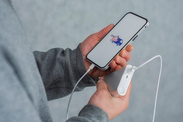 Ekspresowa dostawa w twoim telefonie. mężczyzna trzyma w rękach smartfon z power bankiem i ikoną na białym ekranie.