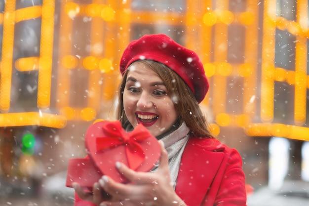 Ekspresyjna blond kobieta nosi czerwony beret i otwierający płaszcz pudełko w kształcie serca podczas opadów śniegu. miejsce na tekst