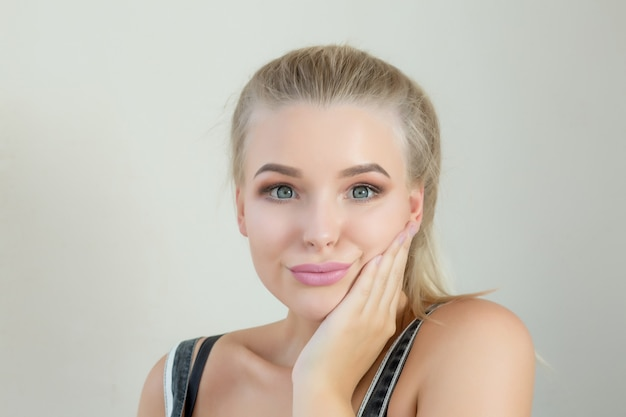 Ekspresyjna blond kobieta z idealnym makijażem pozowanie na szarym tle. miejsce na tekst