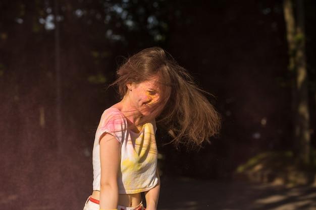 Ekspresyjna brunetka bawi się na festiwalu holi w parku