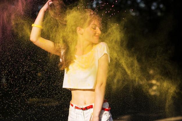Ekspresyjna brunetka kobieta pozuje w chmurze żółtej suchej farby holi w parku