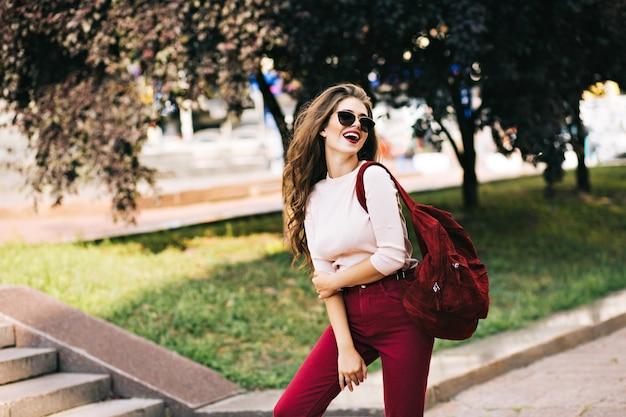 Ekspresyjna dziewczyna z długimi kręconymi włosami pozuje z torbą na wino w parku w mieście. nosi marsala, okulary przeciwsłoneczne i ma dobry nastrój.