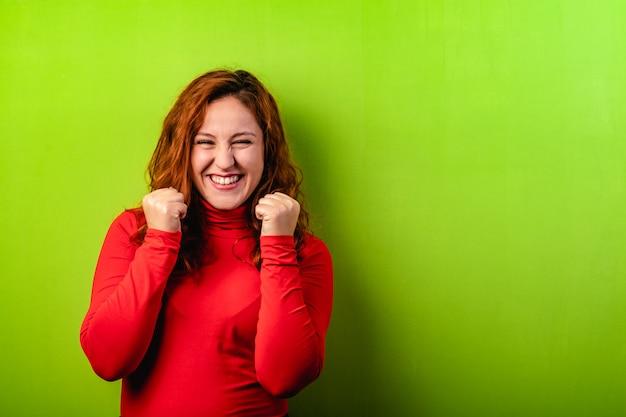Ekspresyjna szczęśliwa rudzielec kobieta na zielonym tle