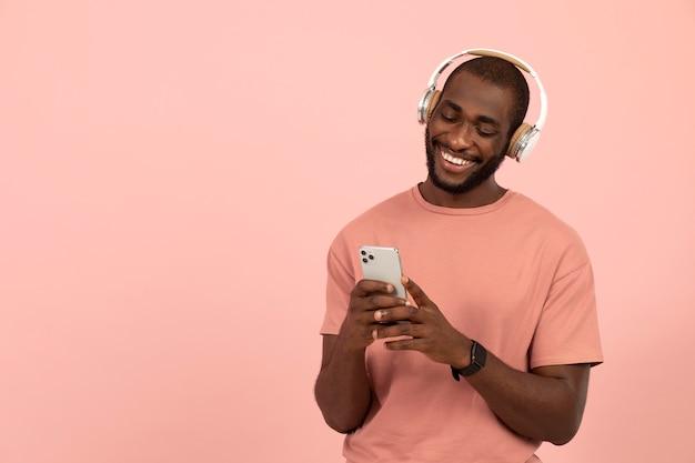 Ekspresyjny afroamerykanin słuchający muzyki na słuchawkach