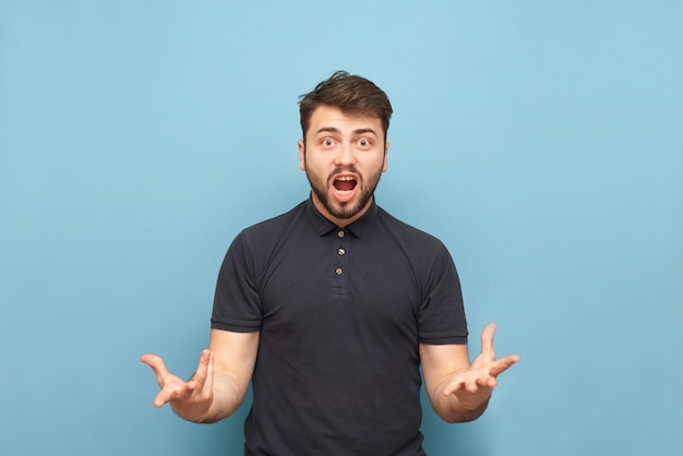 Ekspresyjny brodaty mężczyzna w ciemnej koszulce raduje się na niebiesko