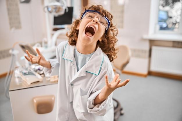 Ekspresyjny chłopiec z kręconymi włosami przebrany za lekarza, trzymający ręce w powietrzu, grając szalonego naukowca