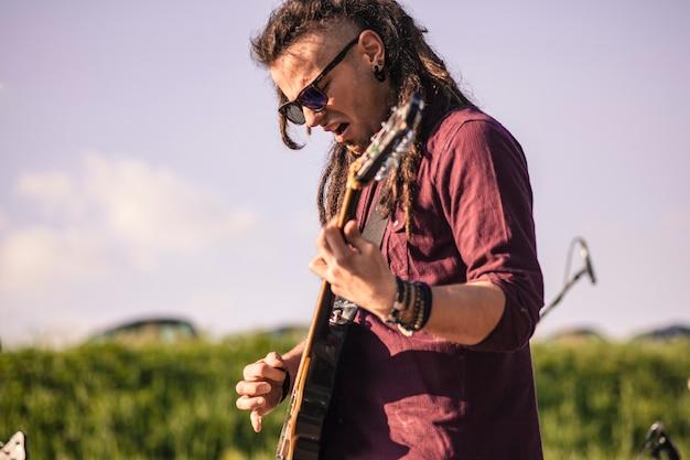 Ekspresyjny gitarzysta pokazuje swoje ekspresje, a zaangażowany w muzykę występuje na żywo.