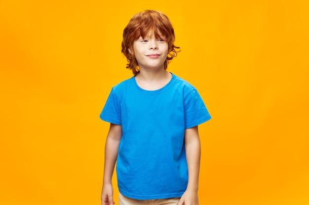 Ekspresyjny mały chłopiec pozowanie w studio