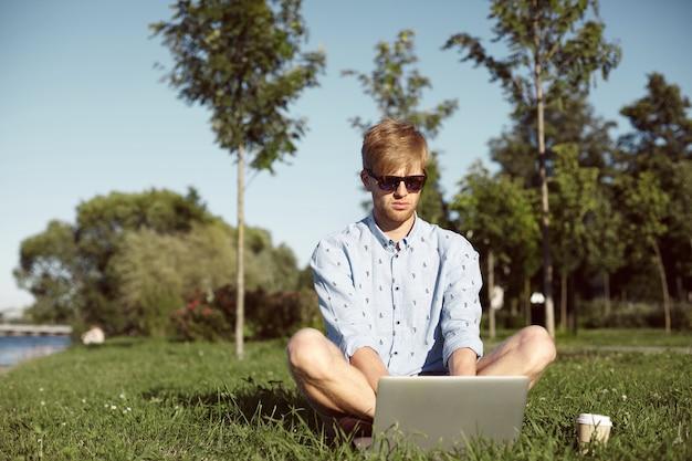 Ekspresyjny mężczyzna jest w parku ze swoim laptopem