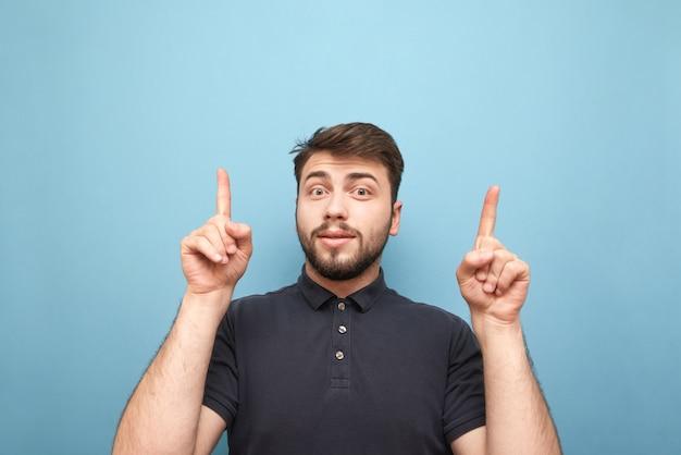 Ekspresyjny mężczyzna z brodą stojący na niebiesko ze zdumioną twarzą i pokazujący palce w pustej przestrzeni
