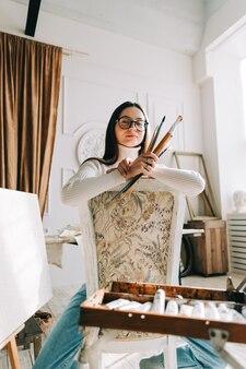 Ekspresyjny młody artysta kobieta pozuje z jej pędzle