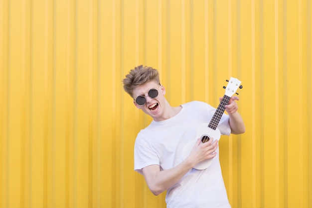 Ekspresyjny młody człowiek bawić się ukulele przeciw żółtej ścianie. muzyk emocjonalny gra na ukulele.