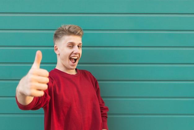 Ekspresyjny młody człowiek stoi na turkusowej ścianie, pokazując kciuk do góry
