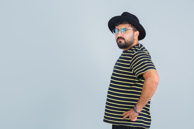 Ekspresyjny młody człowiek stwarzających w studio