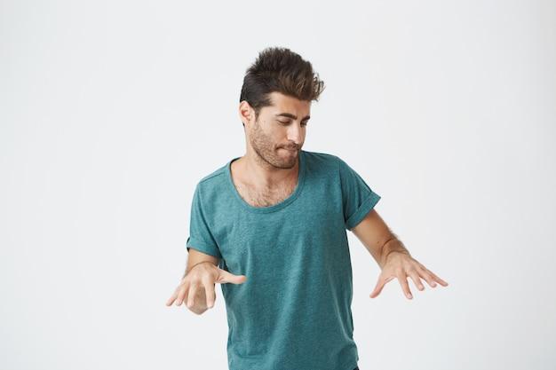 Ekspresyjny młody stylowy hiszpanin ze stylową fryzurą i brodą, ściskający usta, tańczący, wyglądający jak gra na pianinie podczas kręcenia teledysku. język ciała.