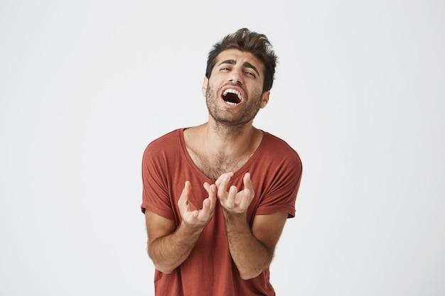 Ekspresyjny nieszczęśliwy młody kaukaski mężczyzna w czerwonej stylowej fryzurze i brodzie, grający niezwykle tragiczny moment w grze uniwersyteckiej. negatywne ludzkie emocje