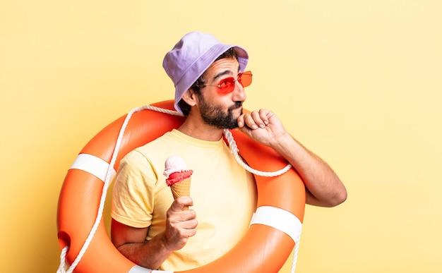 Ekspresyjny szalony brodaty mężczyzna w kapeluszu i okularach przeciwsłonecznych z lodami