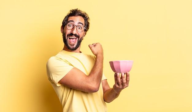 Ekspresyjny szalony mężczyzna czuje się szczęśliwy i staje przed wyzwaniem lub świętuje i trzyma garnek