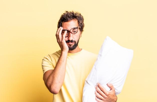 Ekspresyjny szalony mężczyzna czuje się znudzony, sfrustrowany i senny po męczącym i trzymającym poduszkę
