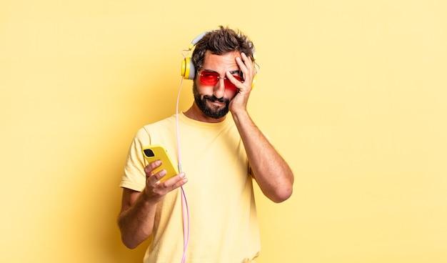 Ekspresyjny szalony mężczyzna czuje się znudzony, sfrustrowany i senny po męczącym ze słuchawkami