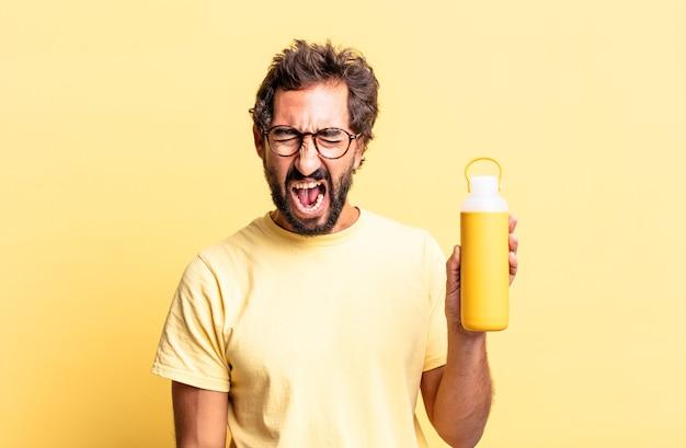 Ekspresyjny szalony mężczyzna krzyczy agresywnie, wygląda na bardzo zły z termosem do herbaty