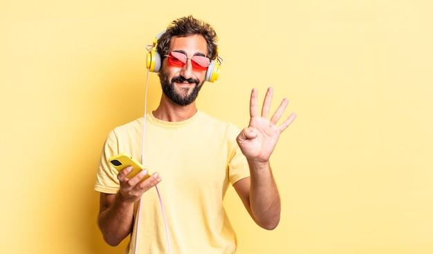 Ekspresyjny szalony mężczyzna uśmiechający się i wyglądający przyjaźnie, pokazujący cyfrę cztery ze słuchawkami