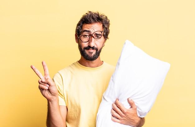 Ekspresyjny szalony mężczyzna uśmiechający się i wyglądający przyjaźnie, pokazujący numer dwa i trzymający poduszkę