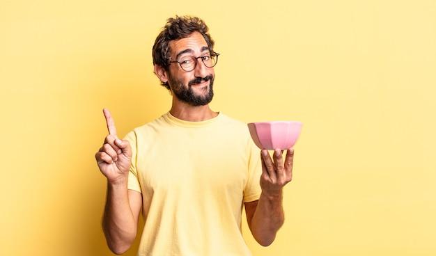 Ekspresyjny szalony mężczyzna uśmiechający się i wyglądający przyjaźnie, pokazujący numer jeden i trzymający garnek