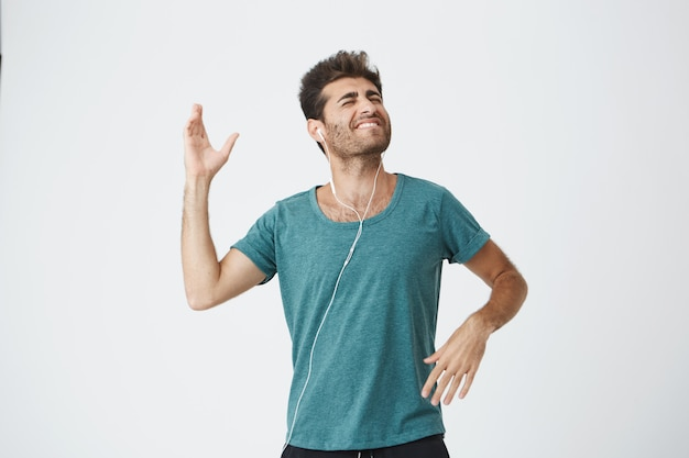 Ekspresyjny uśmiechnięty przystojny młody hiszpan w niebieskiej koszulce, słuchający ulubionej piosenki ze słuchawkami i tańczący radośnie. koncepcja ludzi i stylu życia