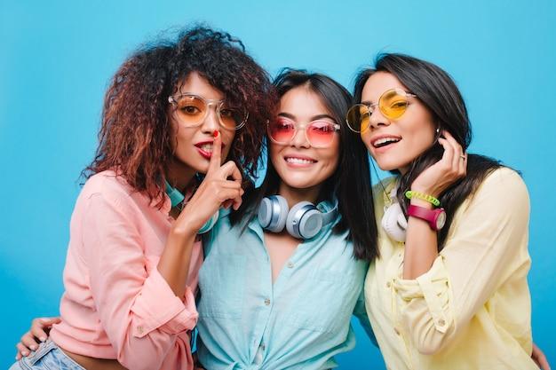 Ekstatyczna azjatka w niebieskiej bawełnianej koszuli obejmująca przyjaciół. kryty portret łapania afrykańskiej damy z kręconymi włosami, zabawy z koleżankami.