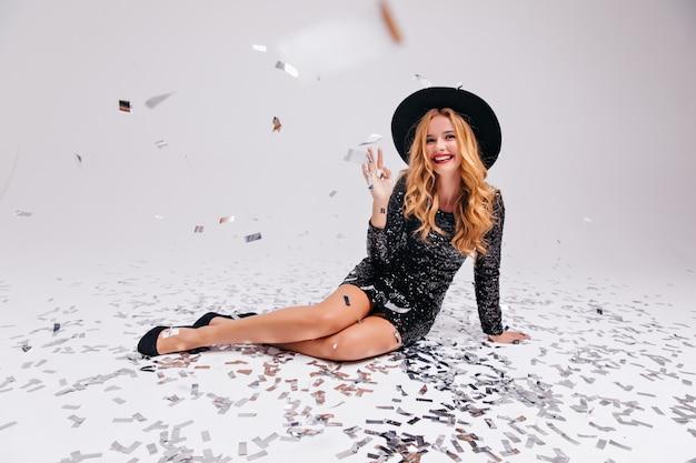 Ekstatyczna blondynka w czarnej sukni siedzi na podłodze. zainteresowana czarująca dziewczyna zabawy na imprezie.