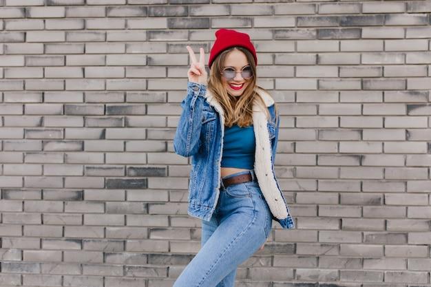 Ekstatyczna blondynka w czerwonym kapeluszu stojąca w pewnej pozie obok ściany z cegły. odkryty strzał cute kaukaski kobieta w dżinsy i kurtkę dżinsową, zabawy na ulicy.