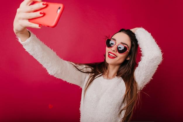 Ekstatyczna brunetka bawi się włosami podczas robienia sobie zdjęcia