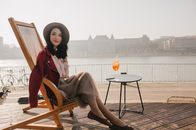 Ekstatyczna brunetka dama pozuje z przyjemnością w szezlongu
