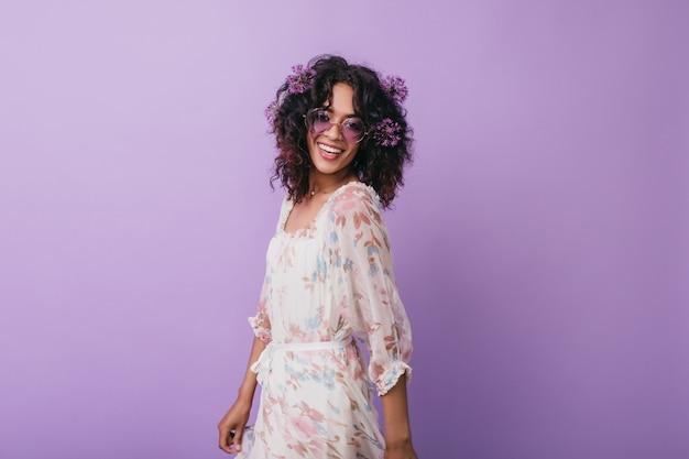 Ekstatyczna czarna dziewczyna w modnej sukience pozuje z radosnym uśmiechem. zadowolony afrykańska modelka nosi kwiaty w falowanych włosach.