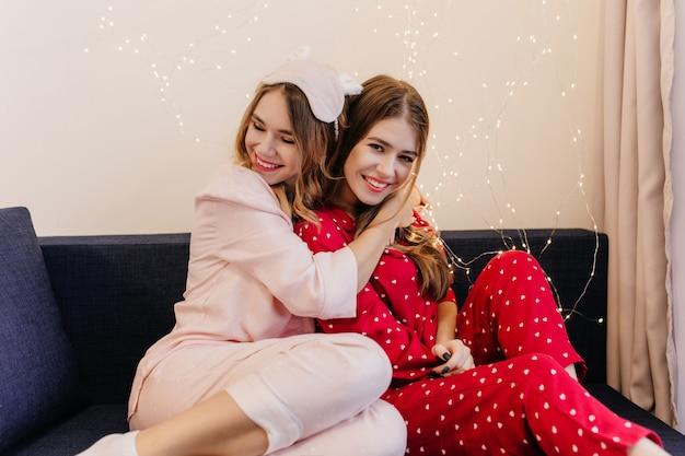 Ekstatyczna dziewczyna w różowej piżamie siedzi na niebieskiej kanapie. śmiejąca się brunetka dama w czerwonym kombinezonie nocnym pozuje, gdy obejmuje ją jej siostra.