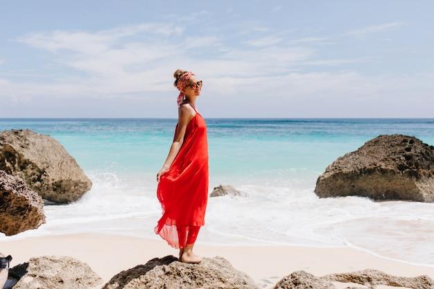 Ekstatyczna dziewczyna z ładnym uśmiechem stojąca na dużym kamieniu z oceanem. pełnometrażowe plenerowe zdjęcie wesołej turystki odpoczywającej na dzikiej plaży.