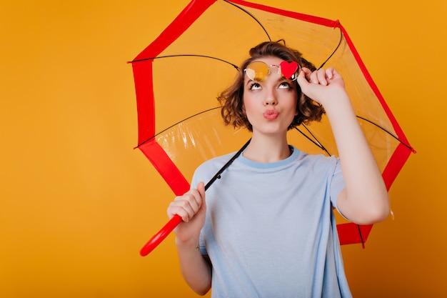 Ekstatyczna dziewczyna z zabawnym wyrazem twarzy, dotykając jej okulary przeciwsłoneczne i patrząc na serduszko. wewnątrz zdjęcie inspirowanej młodej brunetki pozującej z parasolem.