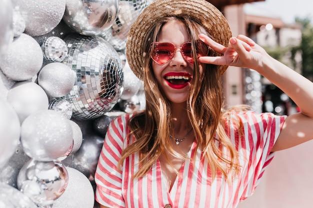 Ekstatyczna europejska dziewczyna śmiejąca się, pozująca obok błyszczących piłek. zewnątrz portret pięknej dobrej humorze pani w słomkowym kapeluszu letnim.