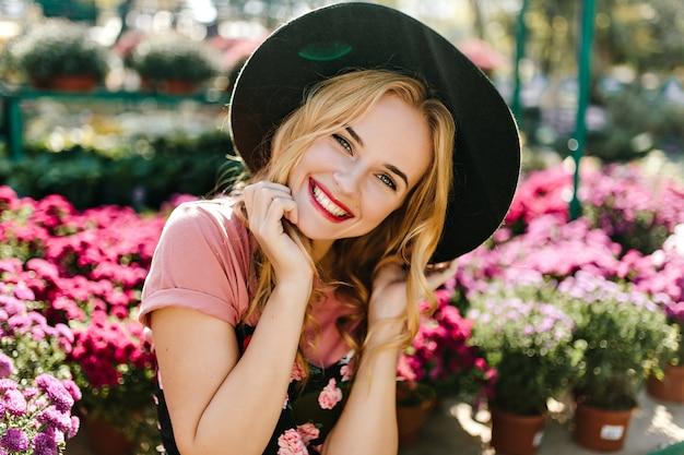 Ekstatyczna kaukaska kobieta chłodzi rano w oranżerii. zainspirowana młoda kobieta w czarnym kapeluszu z różowymi kwiatami