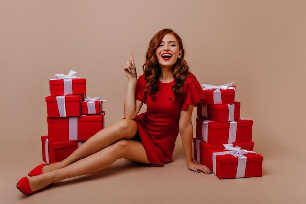 Ekstatyczna kręcona dziewczyna śmiejąca się podczas pozowania przed imprezą noworoczną. zrelaksowana, dobrze ubrana kobieta świętuje urodziny.