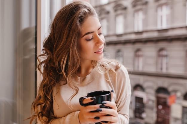 Ekstatyczna kręcona kobieta siedzi z zamkniętymi oczami w pobliżu dużego okna