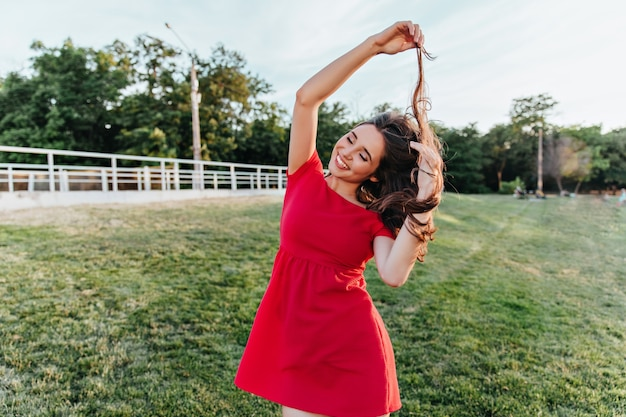 Ekstatyczna młoda dama w letnim stroju bawiąca się włosami podczas sesji zdjęciowej w parku. zewnątrz strzał cute girl w czerwonej sukience zabawy w weekend.