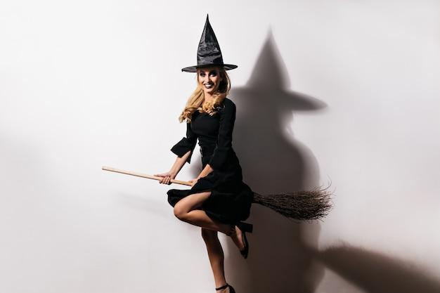 Ekstatyczna młoda kobieta w kapeluszu czarownicy, zabawy w karnawale. kryty zdjęcie eleganckiej kaukaskiej dziewczyny siedzącej na magicznej miotle.