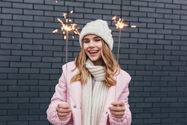 Ekstatyczna modelka w zimowym stroju korzystających z ferii zimowych. plenerowy portret zainspirowanej europejskiej dziewczyny trzymającej bengalskie światła z delikatnym uśmiechem.