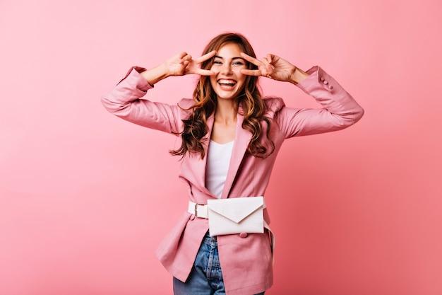Ekstatyczna rudowłosa dziewczyna zabawna pozuje ze znakiem pokoju. ujmująca europejska kobieta relaksująca się podczas sesji portretowej w pomieszczeniach.
