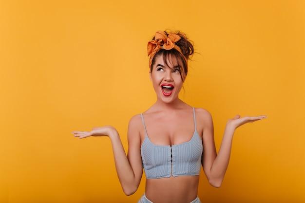 Ekstatyczna zmysłowa dziewczyna stoi z zaskoczonym uśmiechem i pozuje z rękami do góry